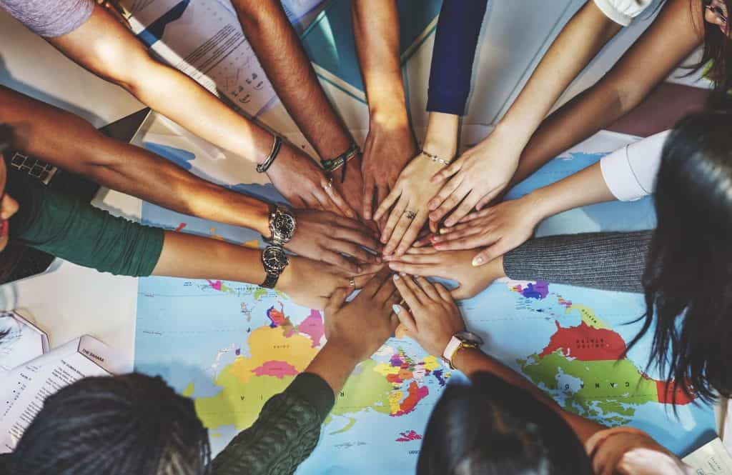 Hands United Over a World Map